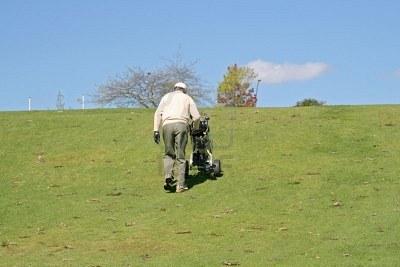 648175-viejo-golfista-que-empuja-su-carrito-cuesta-arriba